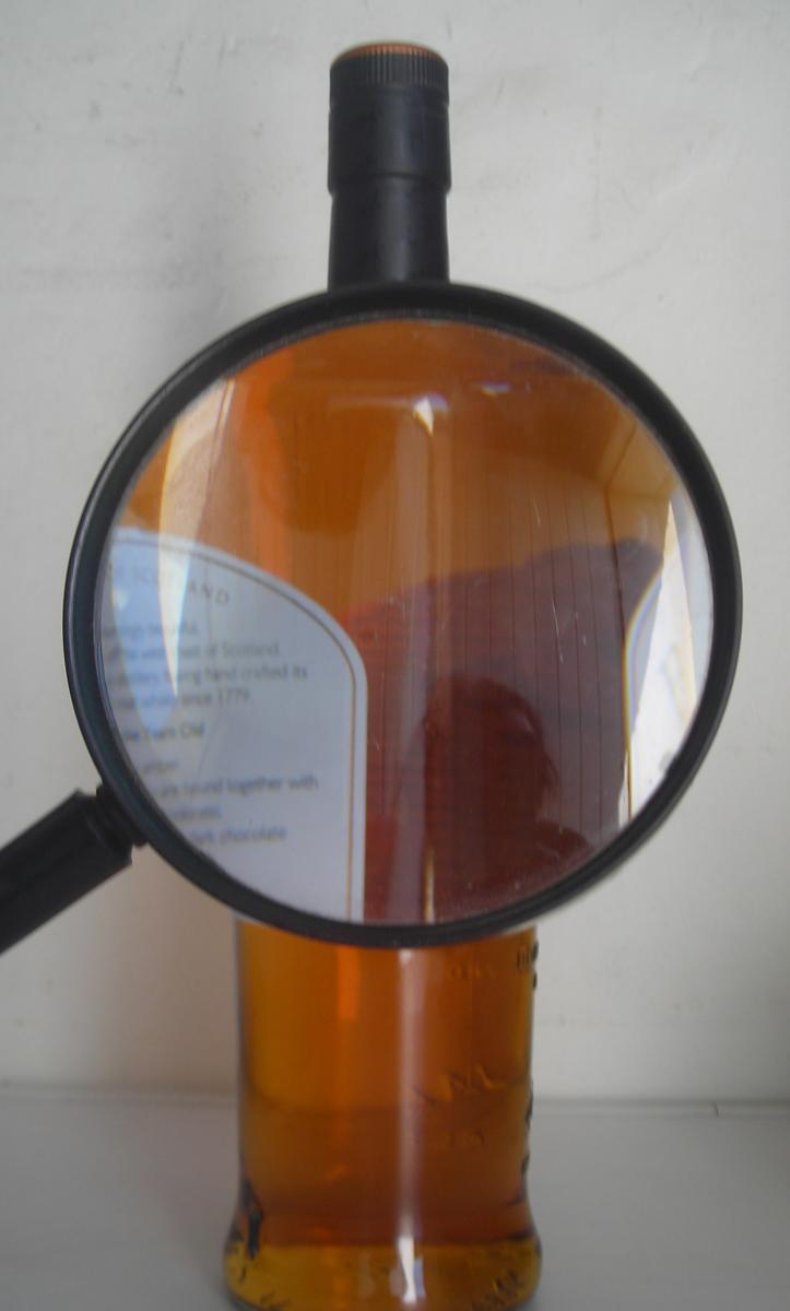 whisky bottle and magnifying glass